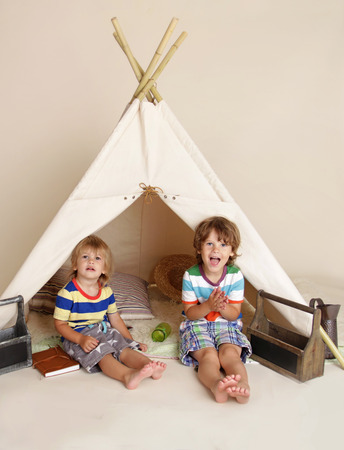 Children, kids playing at home indoors in a teepee tent 版權商用圖片