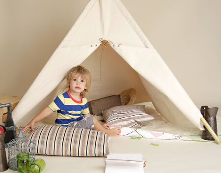 Child playing at home indoors with a teepee tent Stock fotó