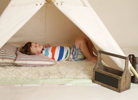creativity: Child playing at home indoors with a teepee tent, taking a nap
