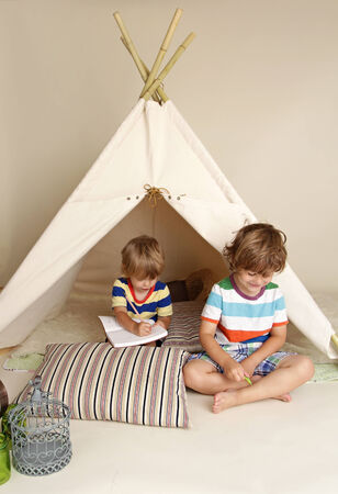 Child playing at home indoors with a teepee tent Фото со стока