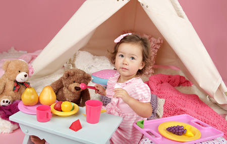 girl friend: Happy toddler girl engaged in pretend play tea party indoors at home with a teepee tent Stock Photo