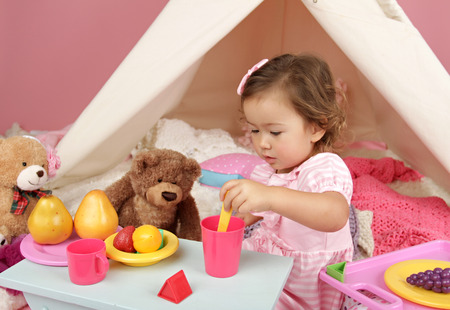 pretend: Happy toddler girl engaged in pretend play tea party indoors at home with a teepee tent Stock Photo