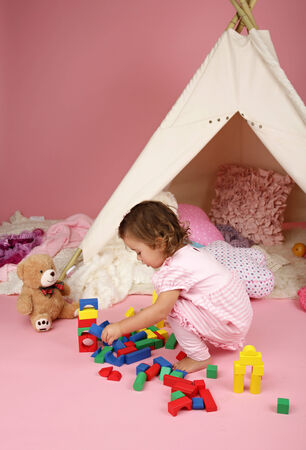 pretend: Happy toddler girl engaged in pretend play at home with blocks