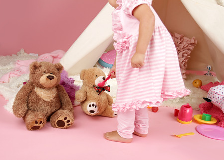 stuffed animals: Happy toddler girl engaged in pretend play tea party indoors at home with a teepee tent Stock Photo