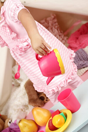 teaparty: Happy toddler girl engaged in pretend play tea party indoors at home with a teepee tent Stock Photo