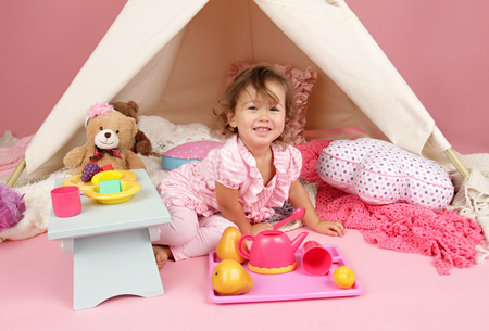 kids play: Happy toddler girl engaged in pretend play tea party indoors at home with a teepee tent Stock Photo