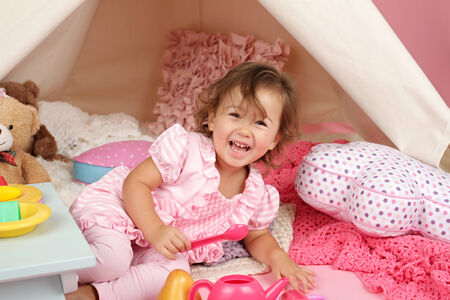 engagement party: Happy toddler girl engaged in pretend play tea party indoors at home with a teepee tent Stock Photo
