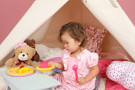 Happy toddler girl engaged in pretend play tea party indoors at home with a teepee tent Фото со стока