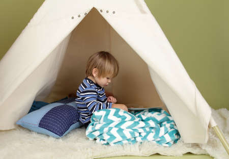 art activity: Child playing at home in a tent, drawing and art activity, showing a blank page Stock Photo