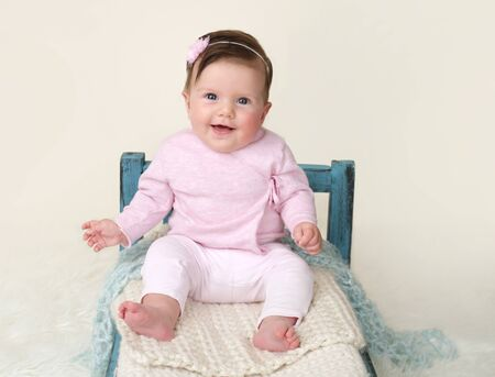 milestones: Happy baby sitting on Bed, milestones and development concept