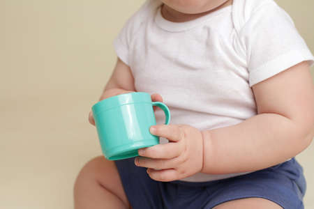 grasp: Child holding a cup, eating or drinking, baby nutrition concept