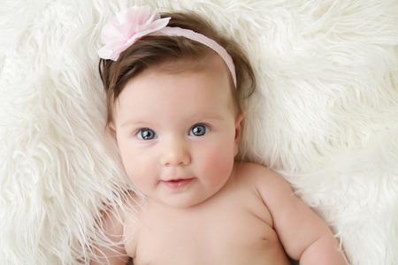 Pasgeboren baby meisje zich in een kom op haar rug, op de deken van bont, glimlachend camera kijken Stockfoto