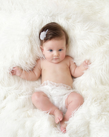 accessorize: Newborn baby girl posed in a bowl on her back, on blanket of fur, smiling looking at camera