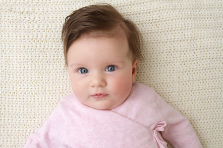 posed: Newborn baby girl posed in a bowl on her back, on knit blanket, smiling looking at camera