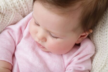 posed: Newborn baby girl posed in a bowl on her back, macro of eye lashes, on knit blanket, smiling looking at camera