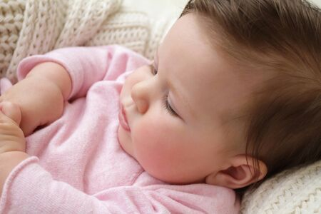 accessorize: Newborn baby girl posed in a bowl on her back, on knit blanket, smiling looking at camera