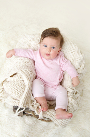 posed: Newborn baby girl posed in a bowl on her back, on knit blanket, smiling looking at camera, wearing comfortable pj pajamas