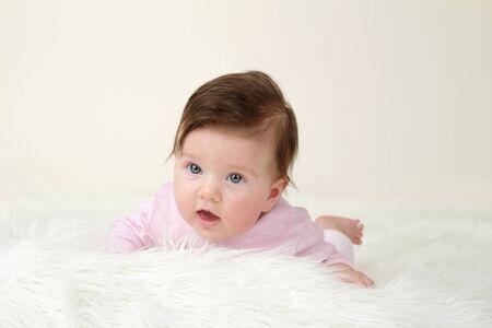 tummy time: Newborn Baby tummy time on white soft fur, blank copyspace Stock Photo