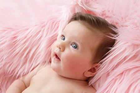 girl portrait: Newborn baby girl posed in a bowl on her back, on blanket of fur, smiling looking at camera