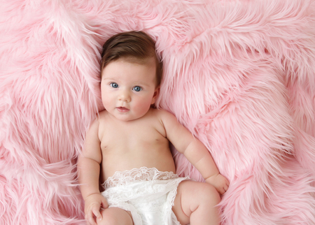 Newborn baby girl posed in a bowl on her back, on blanket of fur, smiling looking at camera photo