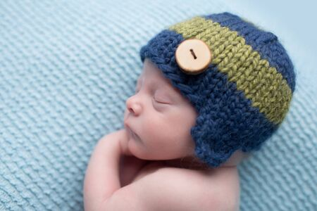 newborn baby boy: Sleeping newborn baby boy, infant, on a blue knit blanket, posed asleep during nap time