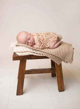 Newborn Baby Asleep, sleeping and taking a nap on a rustic wood chair, posed and curled up