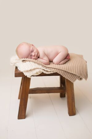 curled up: Newborn Baby Asleep, sleeping and taking a nap on a rustic wood chair, posed and curled up