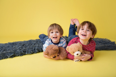 stuffed animals: Two happy kids, brothers or friends, having fun, playing games, and hugging their stuffed toys