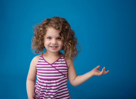 Happy smiling laughing child looking at camera: girl with curly hair pointing at something or holding something