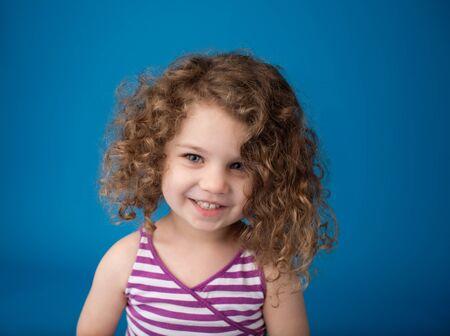hair curly: Feliz sonriente riendo niño mirando a la cámara: chica con el pelo rizado que sostiene las flores, Pascua, primavera o verano tema Foto de archivo