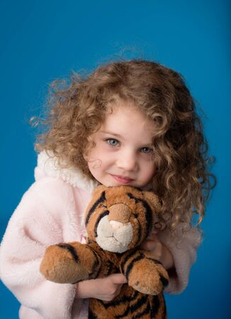 сooking: Happy smiling laughing child looking at camera: girl with curly hair holding flowers, Easter, spring or summer theme Stock Photo