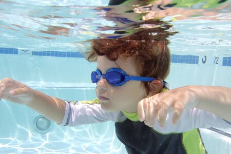 Child swimming in pool underwater, summer or sports theme