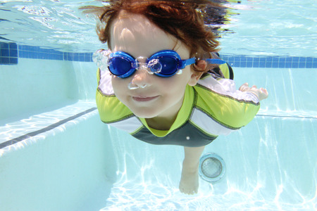 Child diving and swimming in pool underwater, summer or sports theme Stockfoto