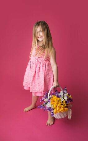 Smiling girl standing with a basket of spring flowers looking at the camera, pink background