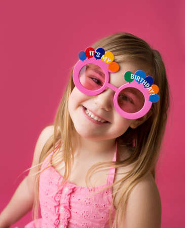 Happy smiling girl in Happy Birthday pink sunglasses laughing and looking at the camera