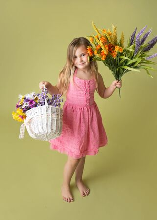 Happy smiling girl standing with a bunch of spring flowers in a basket looking at the camera, green background