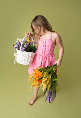 Smiling girl standing with a basket of spring flowers, green background