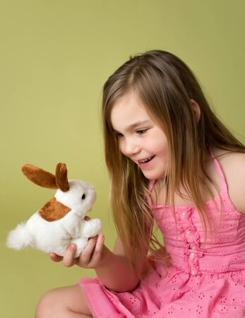 Happy smiling child, girl playing with Easter Bunny