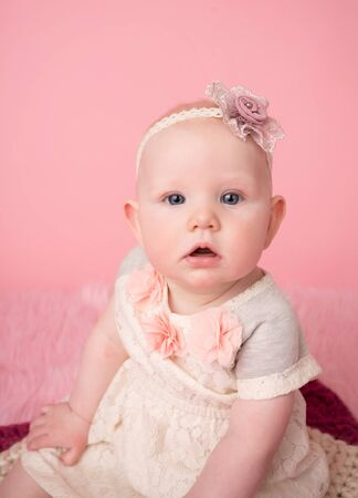Adorable baby girl sitting looking at the camera, child development milestone