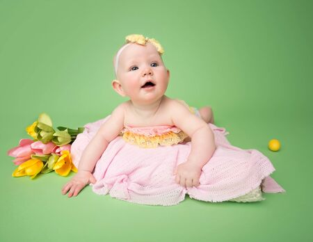 Baby in Easter outfit on her tummy, easter egg and flowers