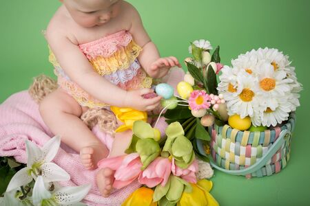 Baby in Easter outfit, holding Easter eggs, tulip flowers on pink blanket Фото со стока