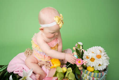 Baby girl on pink background holding an easter egg