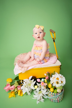Baby girl in Easter outfit with Easter Eggs, and tulip flowers, sitting in a yellow cart