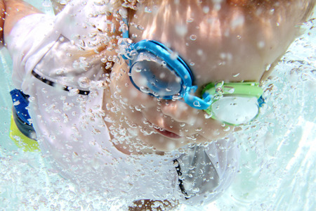 Child  diving and swimming in pool underwater, summer or sports theme Фото со стока