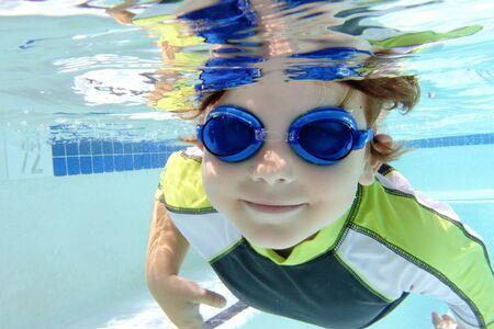 swim: Niño, niño, el buceo y la natación en la piscina bajo el agua, tema del verano o los deportes Foto de archivo