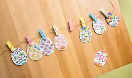Easter activities and crafts project: colorful easter eggs decorated with pencils and markers and stickers, made into a banner