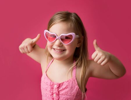 Happy smiling girl in heart shaped pink glasses giving thumbs up; success or achievement