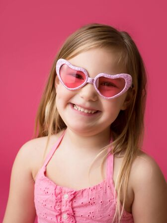 Happy smiling girl in heart shaped pink glasses looking at camera