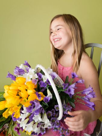 Happy smiling girl with a bunch of spring flowers in a basket looking at the camera, green background