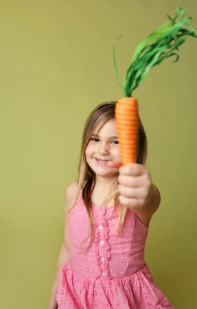 Happy smiling girl holding a carrot, for feeding Easter Bunny, spring, seasonal theme